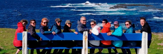 A Vagabond group smiling and seated on a blue bench in a scenic coastal location in Ireland