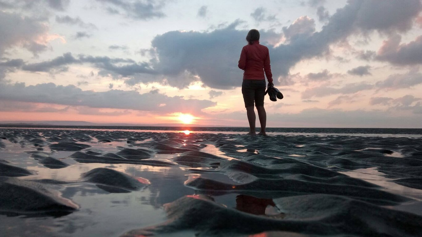 A woman standing on a beach with the back to the camera as the sun is setting