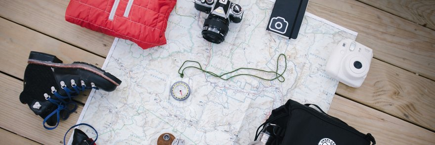 A selection of hiking materials including boots and a red fleece on a map