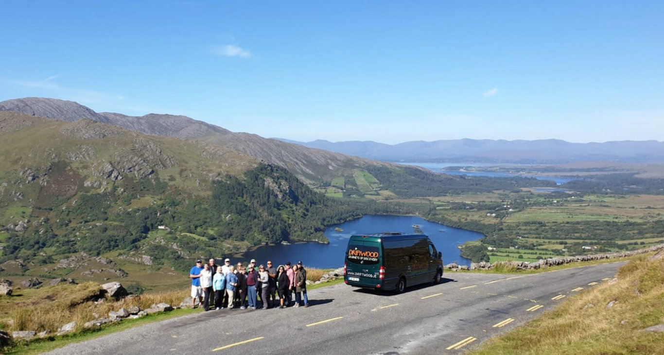 Driftwood group standing beside the bus overlooking the scenery of the healy pass