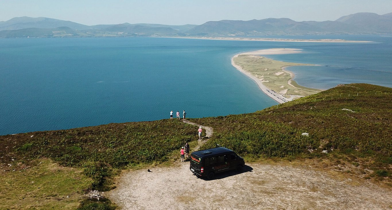 A panoramic view of Rossbeigh beach from a viewing point above it and a vagabond vehicle parked up with guests overlooking the view
