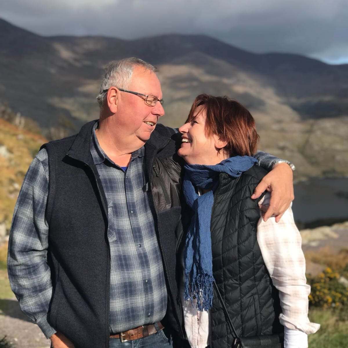 Middle aged couple look into each other's eyes in a scenic location in Ireland