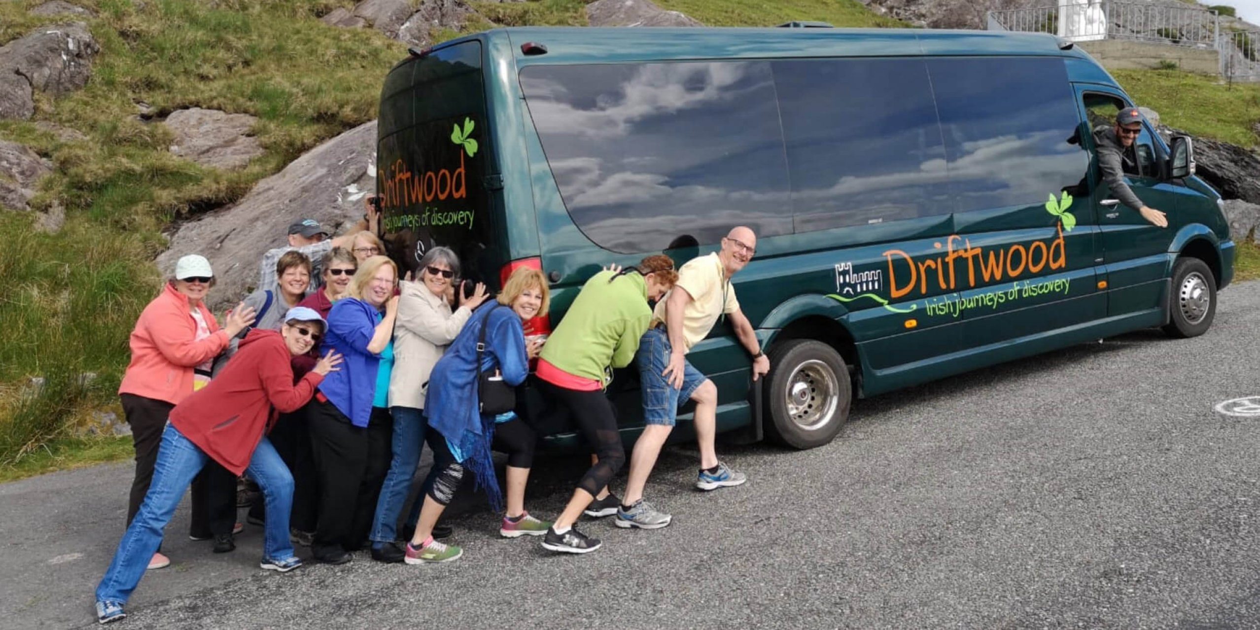 A funny photo of a group of Driftwood guests pretending to push their Drifter tour vehicle uphill