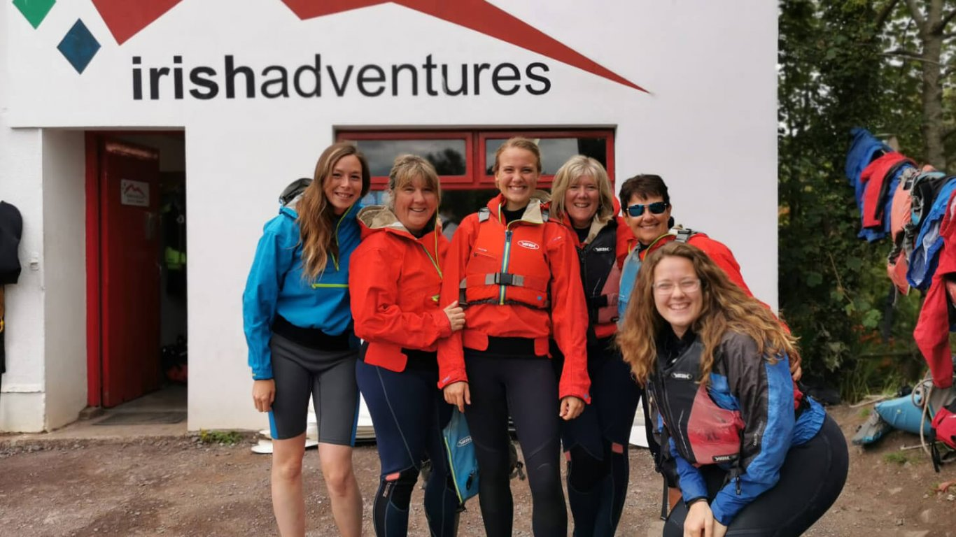 Group of female tour guests smiling and wearing kayaking gear in Ireland