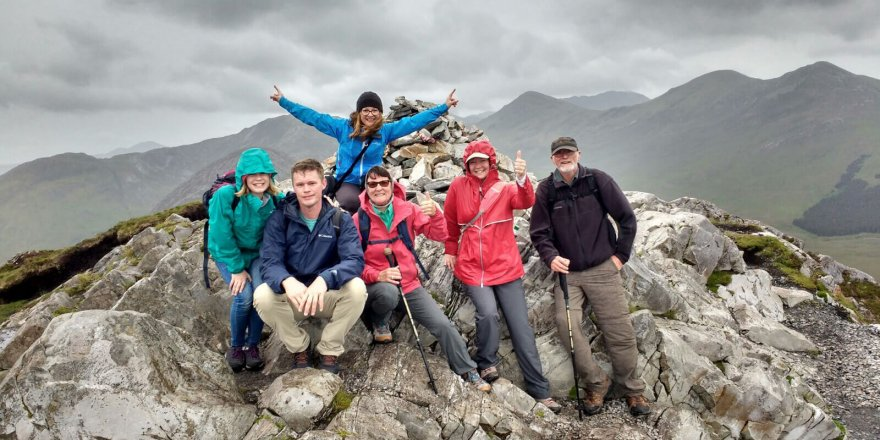 Colourful group posing at the summit of Diamond Hill in Connemara