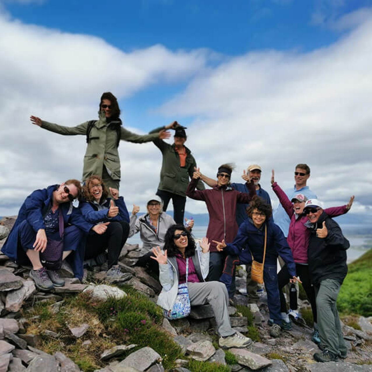 Vagabond group posing with their arms in the air at a viewing point in Rossbeigh