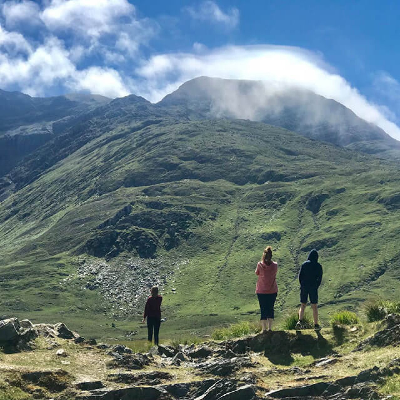 Three guests standing in front of Mweelrea mountain taking picture