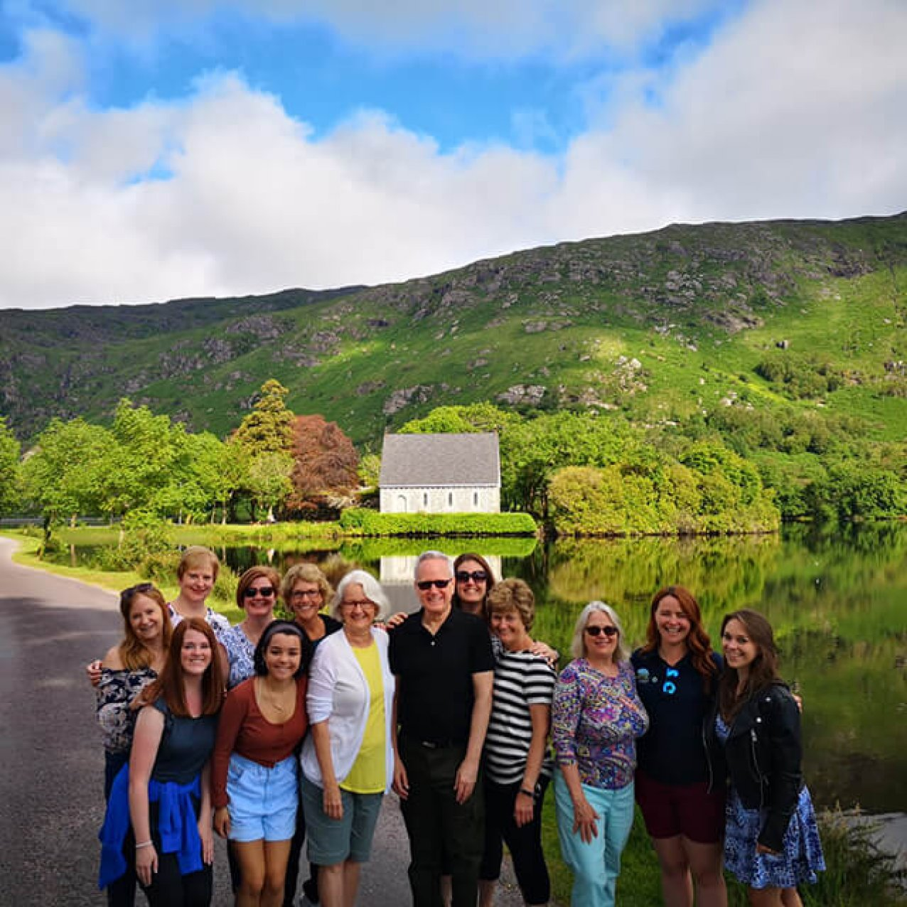 A Driftwood group taking a group photo in front of the lake at Gougane Barra