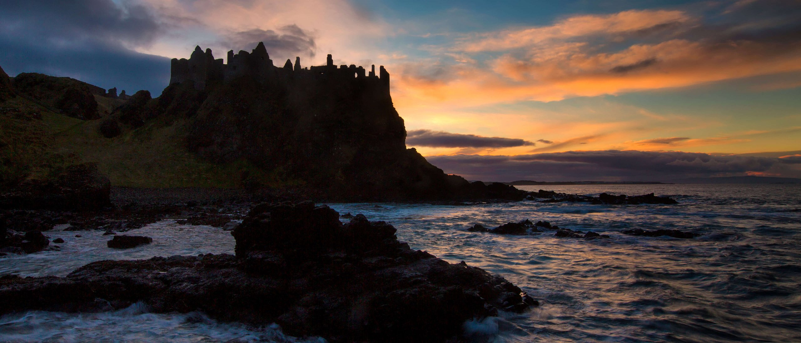 Dunluce Castle on Northern Ireland's Causeway Coast silhouetted against the setting sun with dramatic colours in the sky and ocean in the foreground