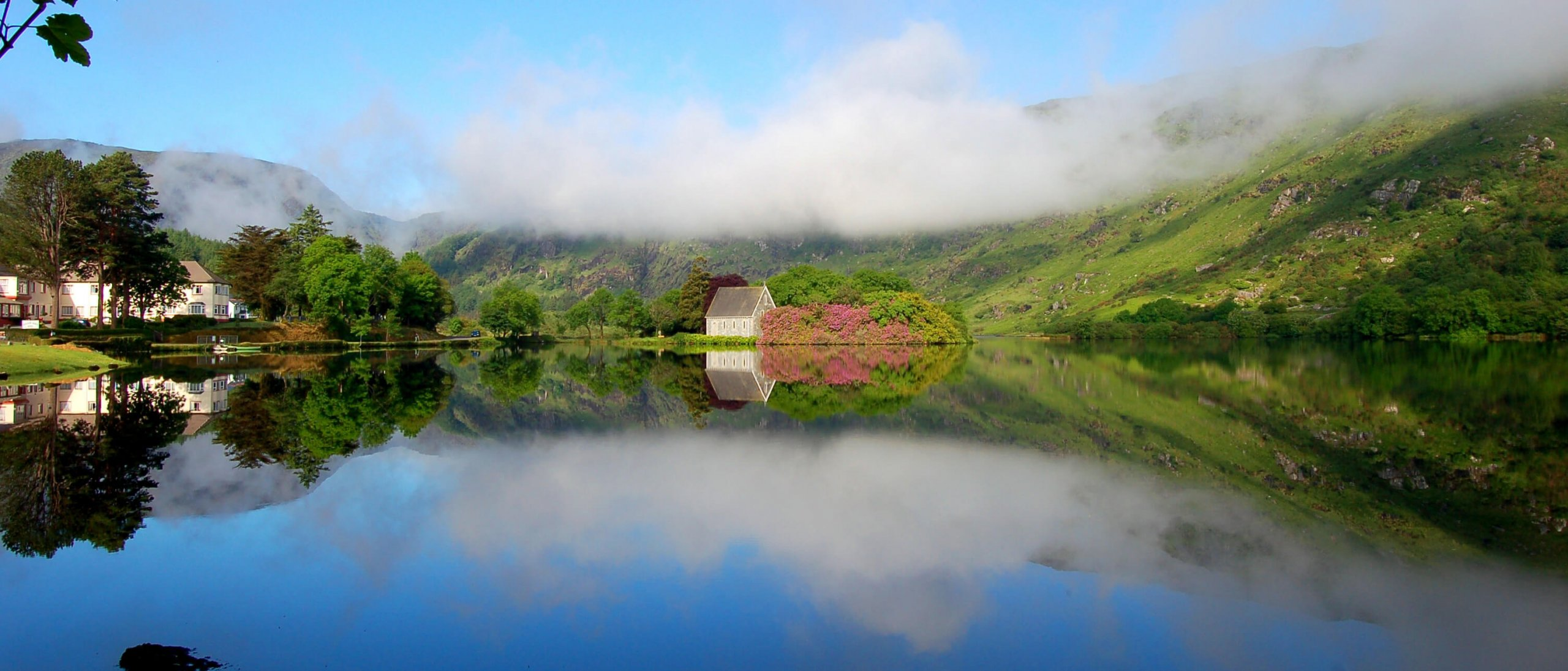 Scenic church and reflection of blue sky, clouds and green mountains in lake at Gougane Barra, Ireland