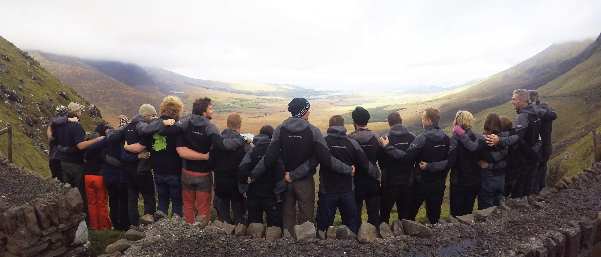Panoramic shot of Vagabond Tour Guides link arms with their backs to the camera with a scenic valley in Ireland in the background