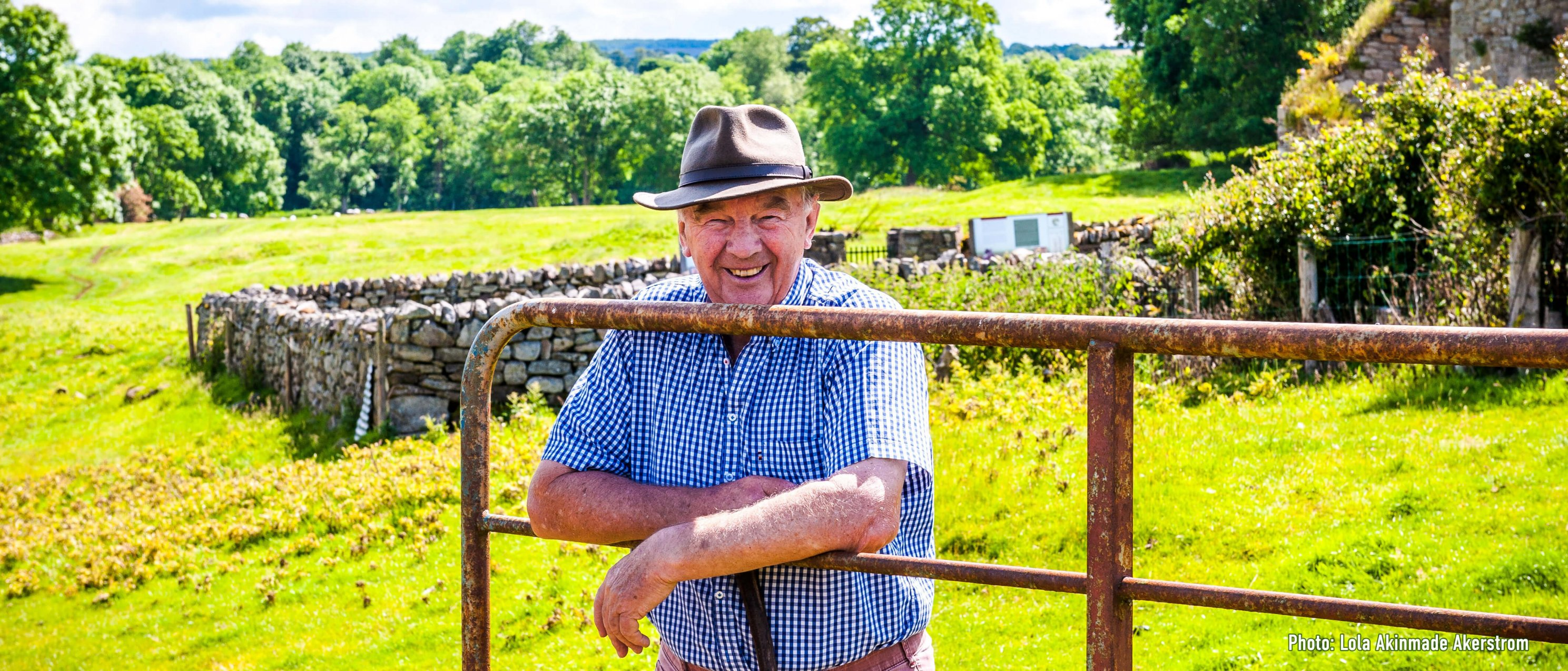Smiling Irish male middle aged tour guide with a hat leaning on gate at Jerpoint in Kilkenny, Ireland
