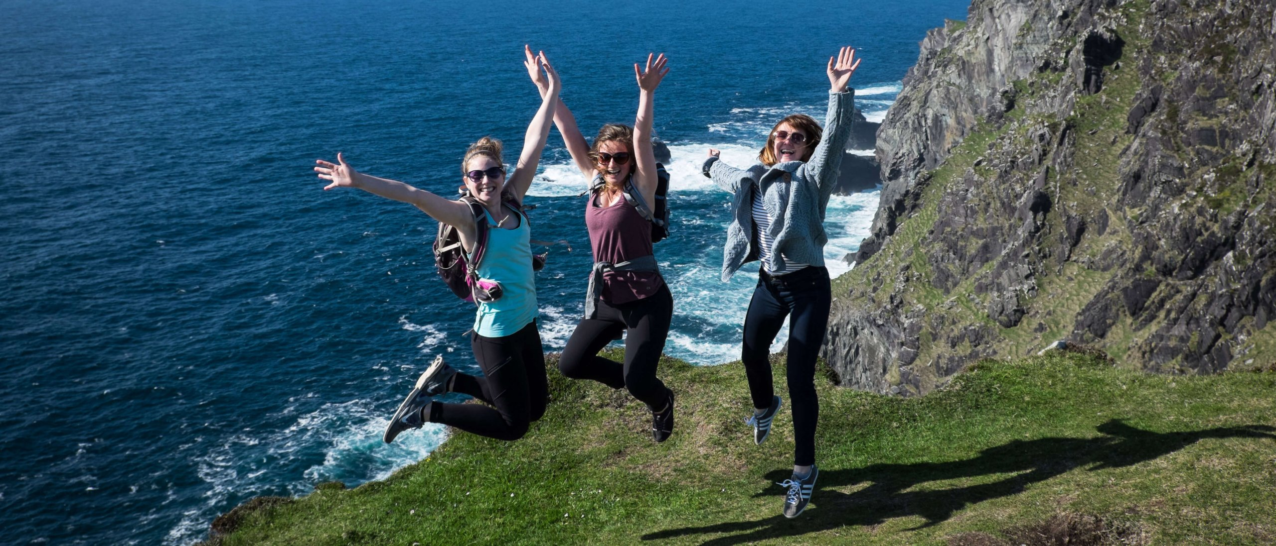 Three Vagabond guests jumping for joy on Bray Head, Wild Atlantic Way, Kerry in Ireland