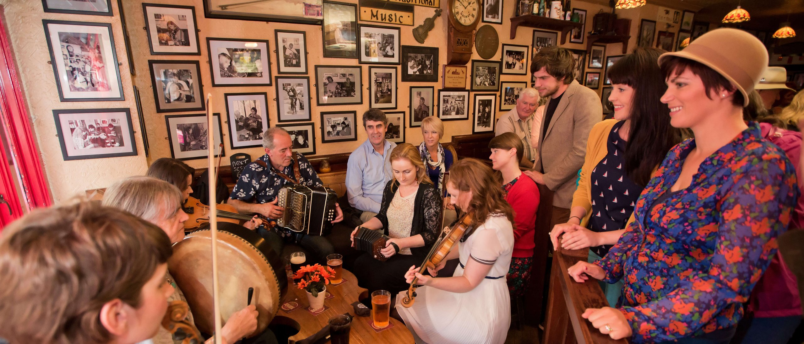A group of musicians perform traditional Irish music while tourist look on