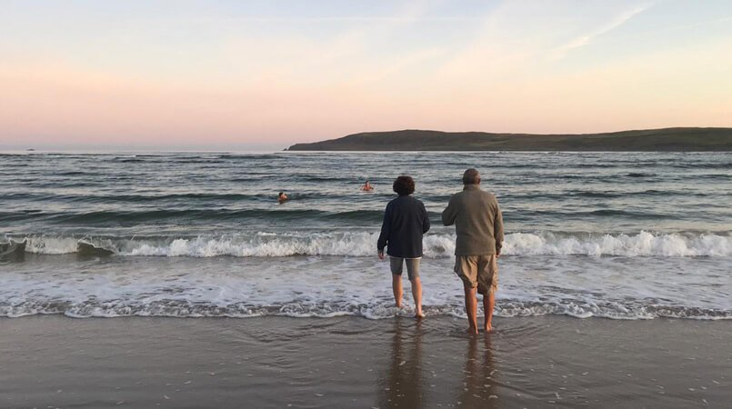 A couple watch two others swim in the sea in Donegal, Ireland