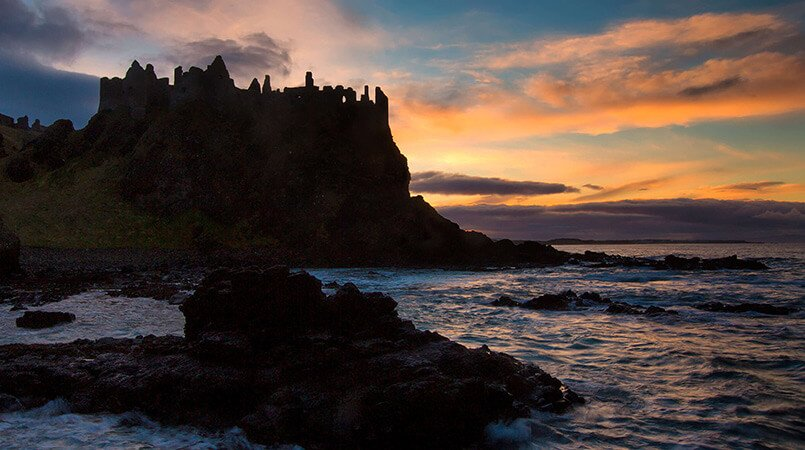 Silhouetted Dunluce Castle on the coast in Ireland