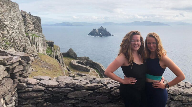 Two females near the summit of Skellig Michael with Little Skellig island in the background