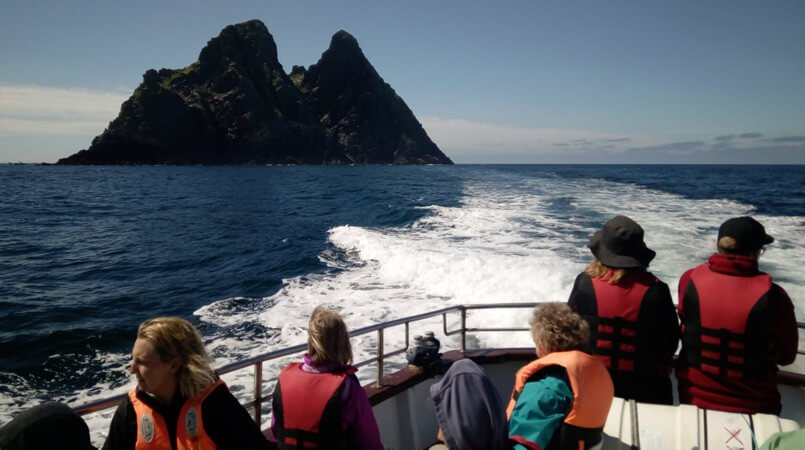 A group watch Skellig Michael island from a moving boat in Ireland
