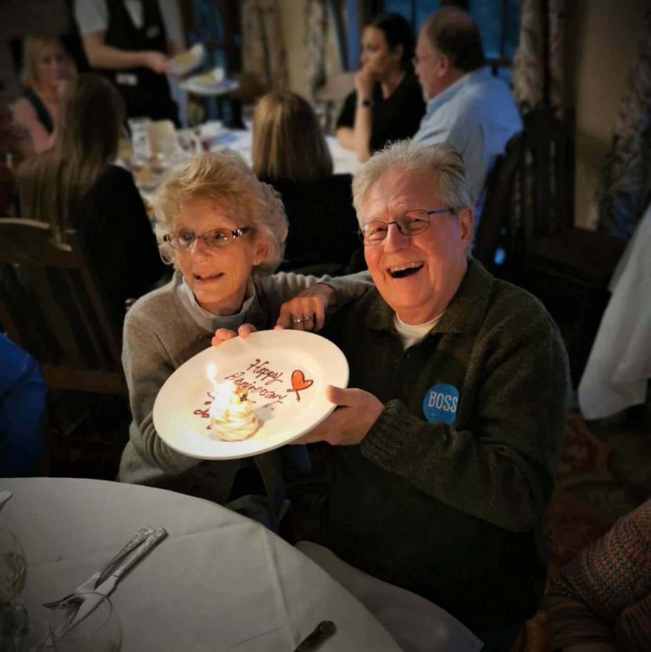 A smiling couple celebrate their 50th anniversary with a cake in Ireland