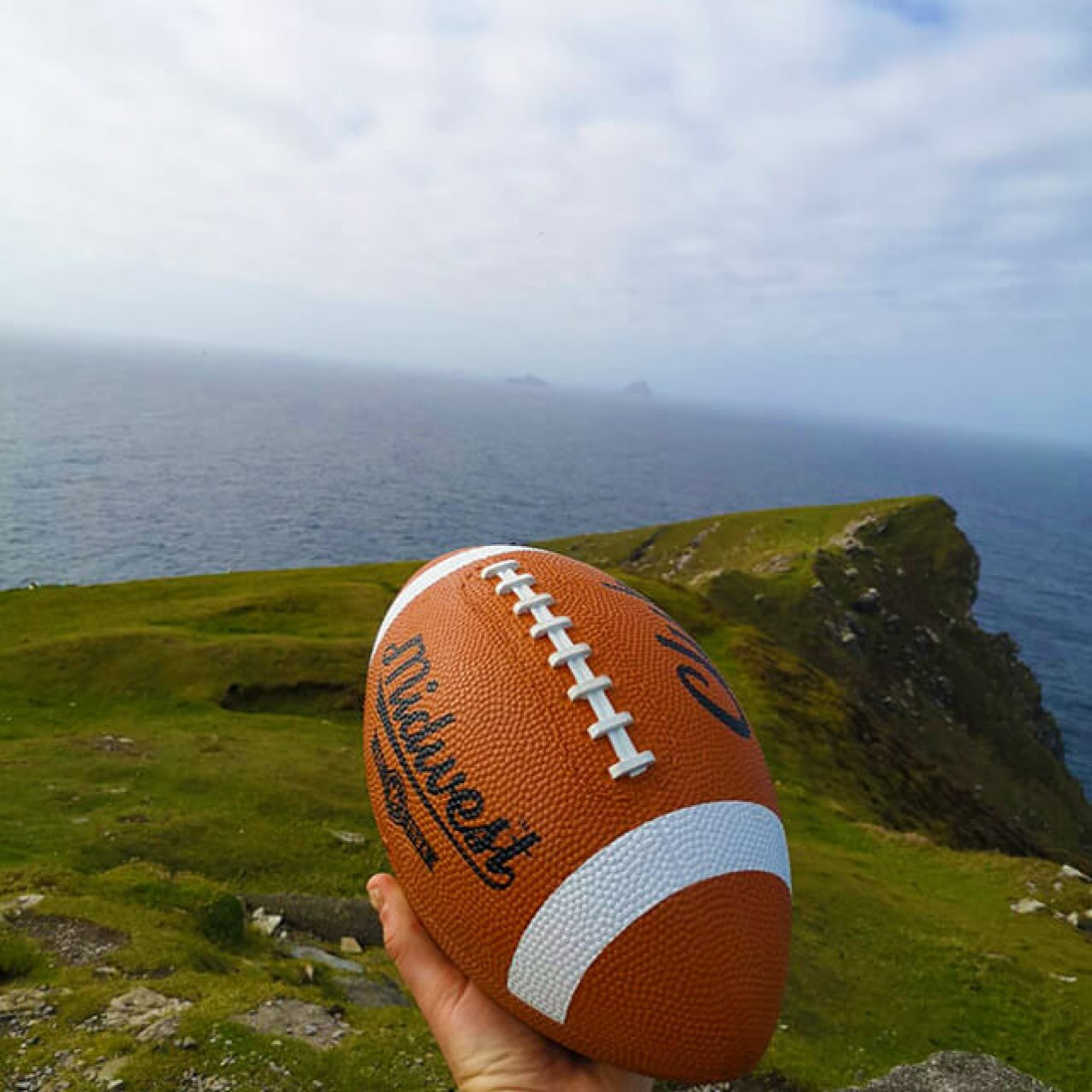 A hand holding an American football on Bray head with a view of the Skellig Islands in the background