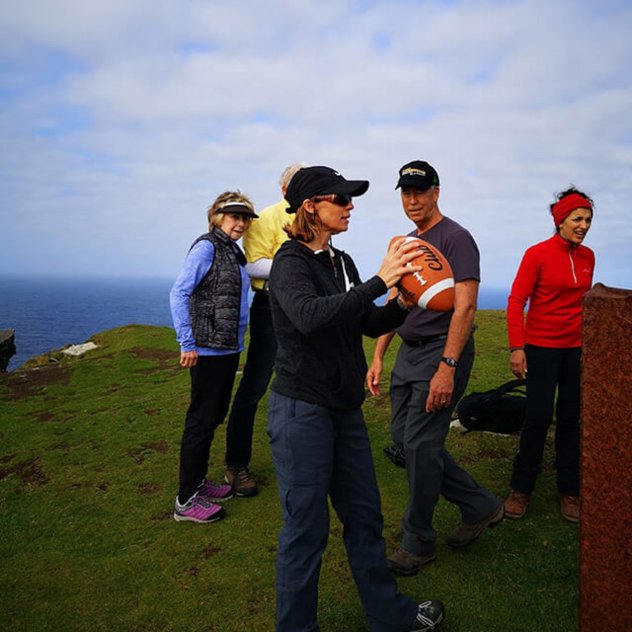 A group of guests on Bray Head with a woman at the front getting ready to throw an American football