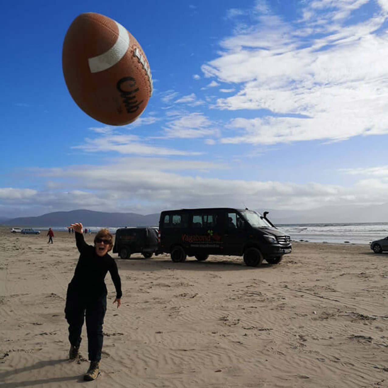 A lady throwing an american football towards the camera on a beach with a Vagabond vehicle in the background