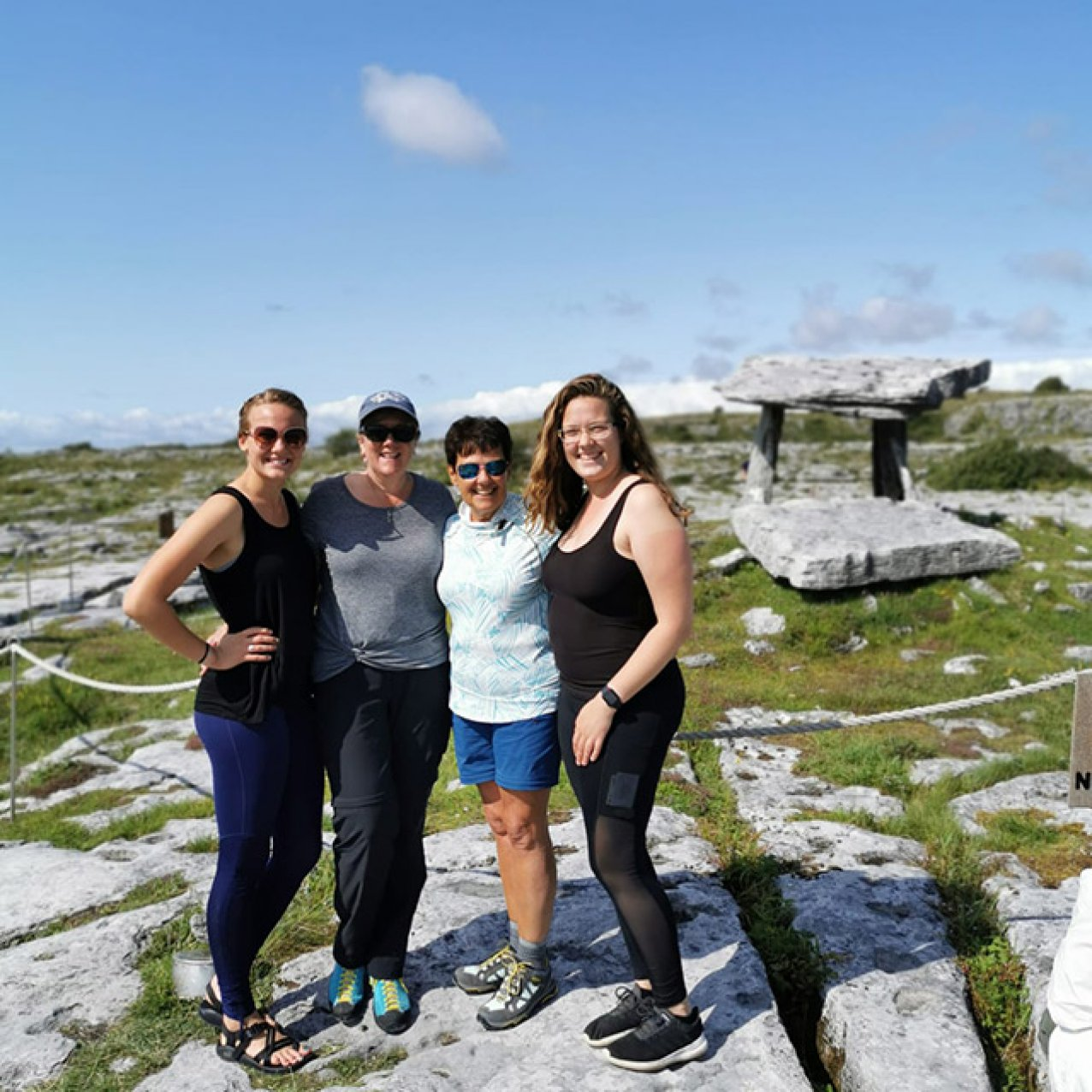 Four ladies posing in front of the Poulnabrone Dolmen