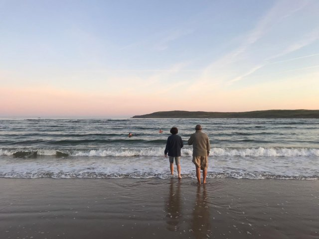A couple enjoying a sunrise on the beach