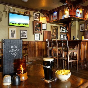 The bar and restaurant in the Wild Atlantic Lodge with the television on and Guinness on the table