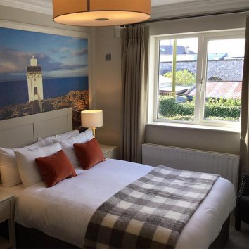 The interior of a main double room in the Wild Atlantic Lodge with a Lighthouse painted on the wall