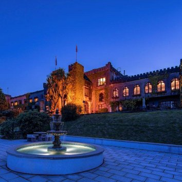 The exterior view of the stunning Abbeyglen Castle Hotel at dusk with water fountain