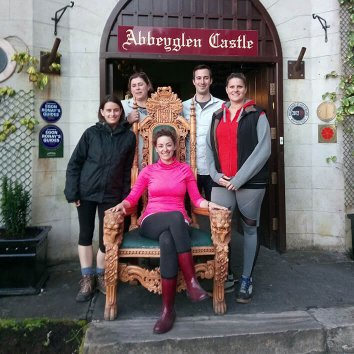 Family posing for a picture with woman sitting on the throne in front of Abbeyglen Castle