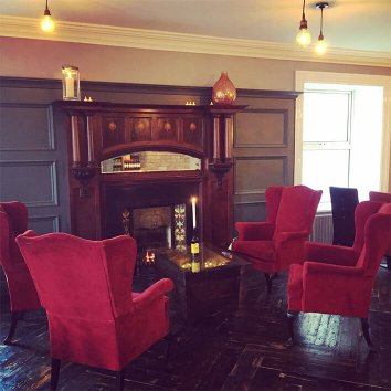 Cosy chairs in front of a fireplace in the living room of Arnolds hotel