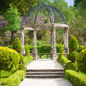A round pergola in the gardens of Ballyseede Castle surrounded by beautiful flowers and trees