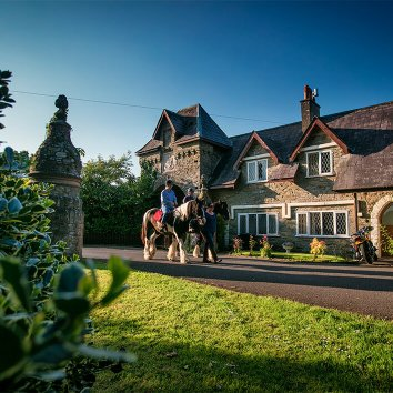 The exterior of Beech Hill with a guest horse riding through the gardens