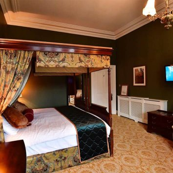 Interior design of main bedroom in Belleek Castle with four poster bed