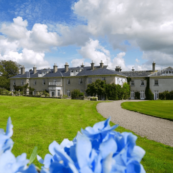 The exterior view of Dunbrody House and Gardens with blue skies and flowers in view