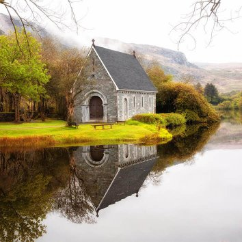 A stunning view of the Gougane Barra Chapel on the Lake with mountains in the background