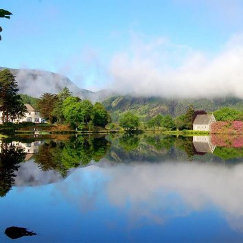 View of Gougane Barra Hotel and the chapel on the side of the lake with the mountains in the background
