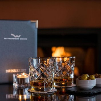 Menus, two whiskeys and olives on the table in front of a warm fire