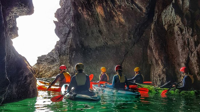 a group of kayakers exploring a sea cave