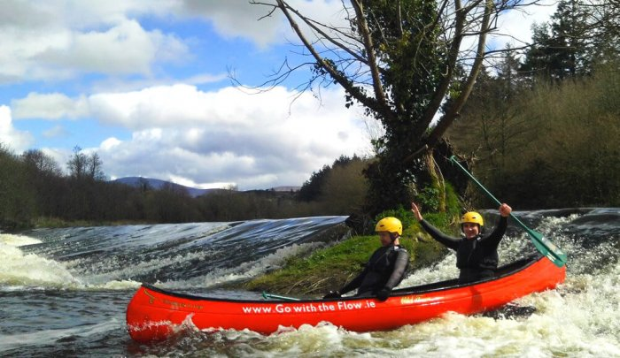 Two people canoe down a weir on the River Barrow in Ireland