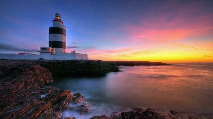Hook Lighthouse on Hook Head peninsula bathed in orange and pink sunrise/sunset light in Ireland