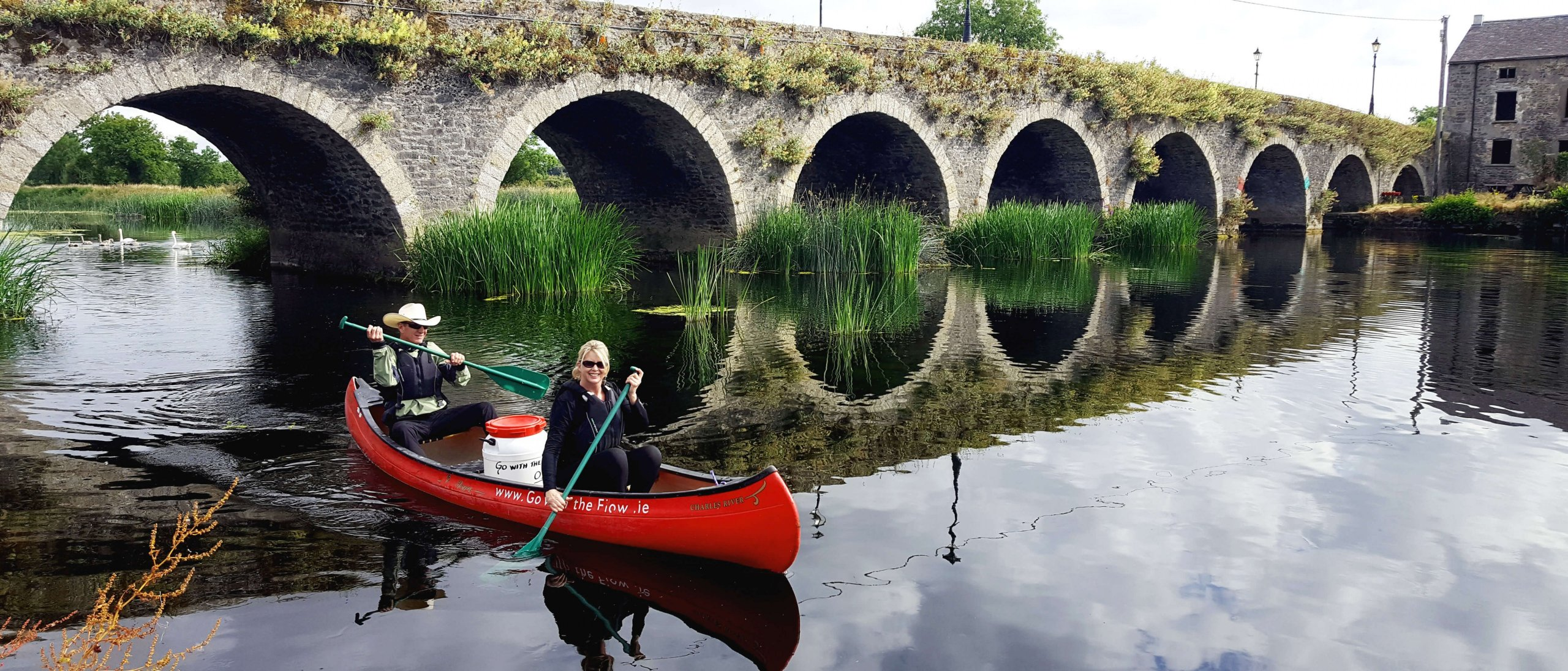 A couple canoe past a multi-arched stone bridge on the River Barrow in Ireland