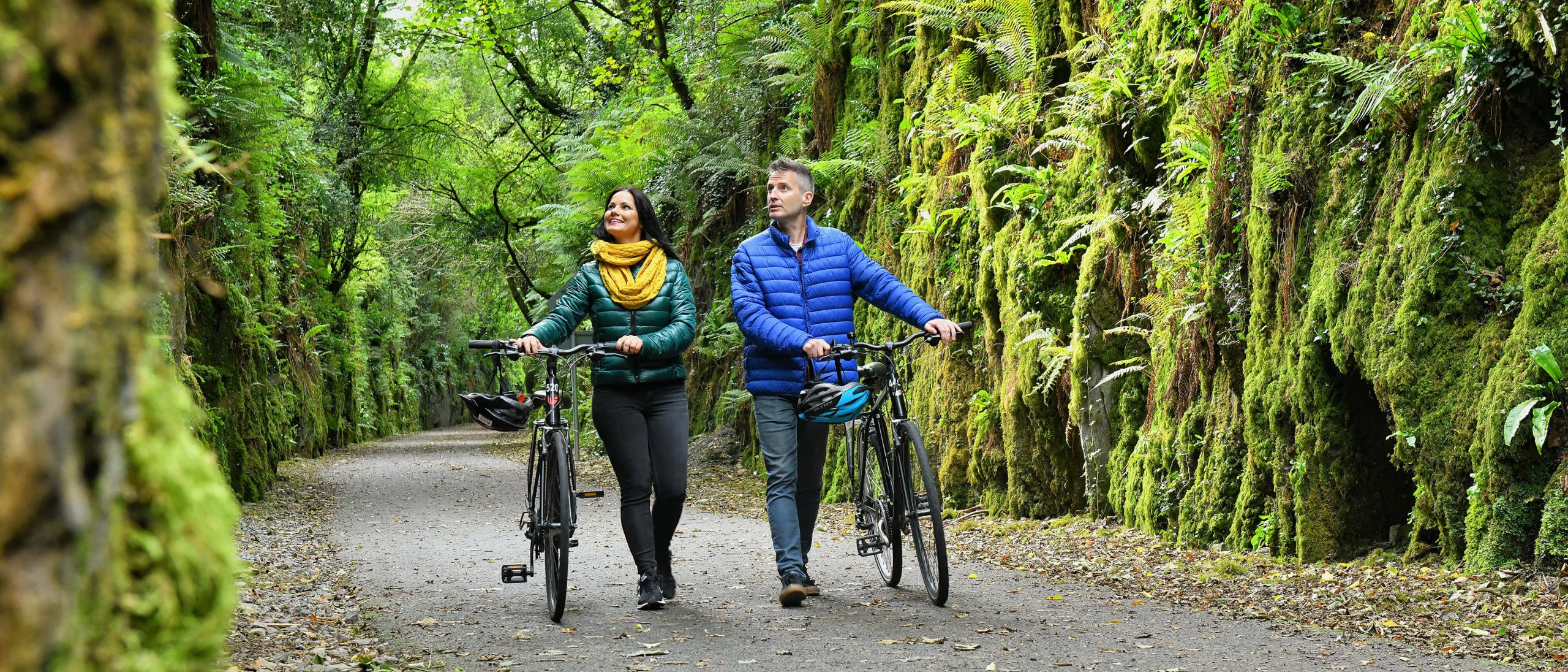 A couple walk with bikes along a moss-covered section of the Waterford Greenway in Ireland