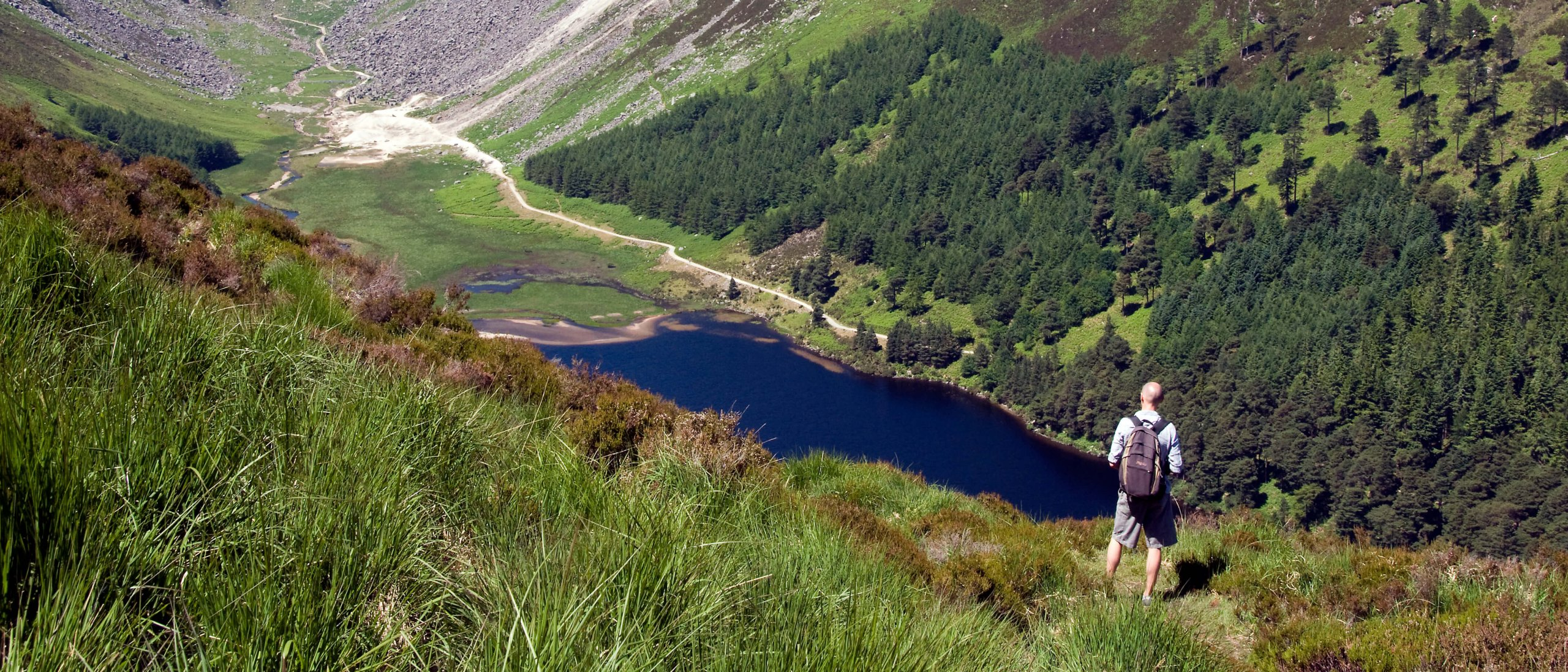Hiker at the summit of the Spink in Glendalough valley, Ireland