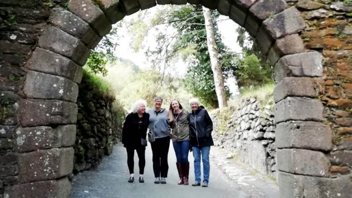 Smiling Driftwood tour group standing in an old arch in Glendalough, Ireland