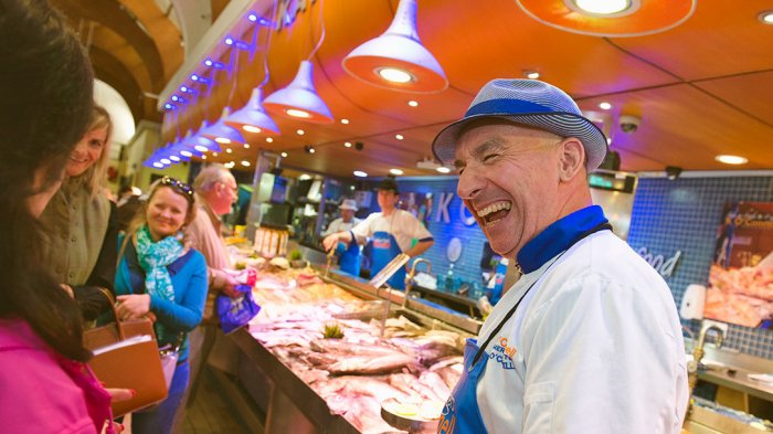 Stallholder laughs with customers at English Market in Cork City