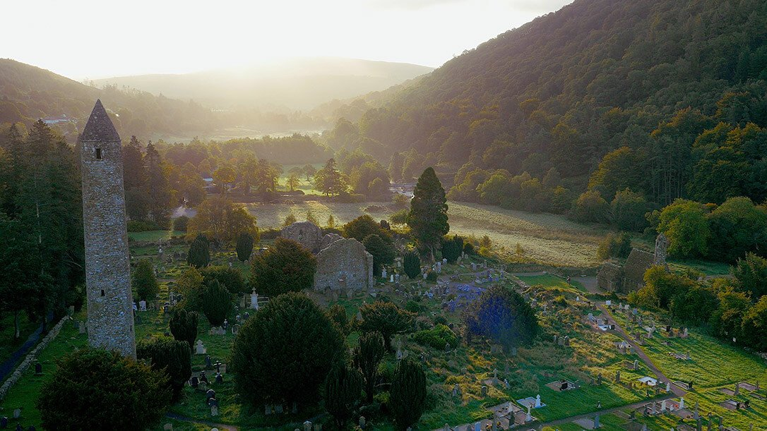 Aerial view of the ancient monastic city of Glendalough including a stone round tower, ruined church and graveyard