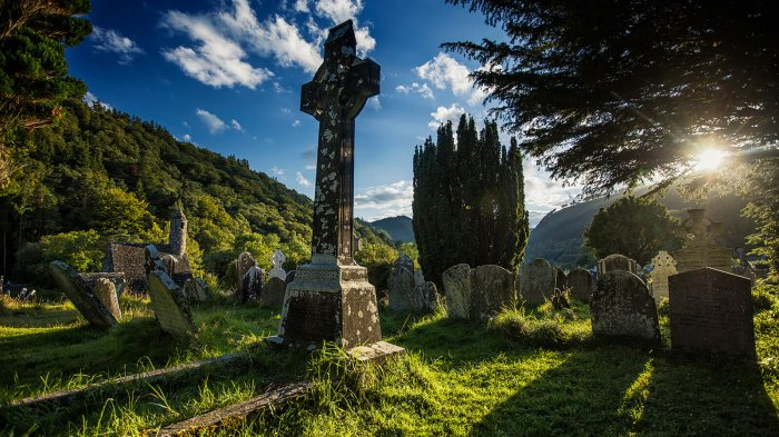Celtic cross gravestone in graveyard with sunlight lens flare in Glendalough, Ireland